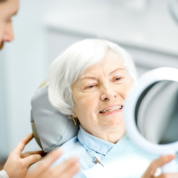 An older woman smiling at herself in the mirror at the dentist office