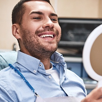 satisfied male dental patient looking at smile in the mirror