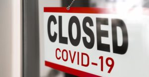 "Door sign that reads ""closed COVID-19"""