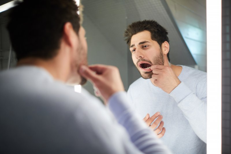 Man checking his gums in the mirror