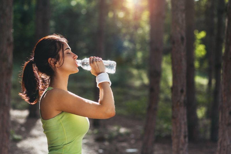 Woman practicing summer oral health tips by drinking water
